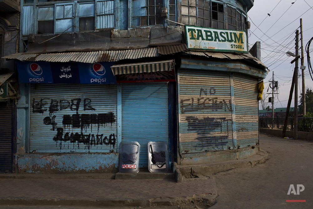 """In this July 23, 2016 photo, graffiti is painted on the security shutters of shops in Srinagar, India-controlled Kashmir. """"Azadi,"""" a Kashmiri word for freedom, and """"India go home!"""" are long-time slogans. People shout them during street protests and spray paint them on walls, although Indian authorities often paint over them. (AP Photo/Bernat Armangue)"""