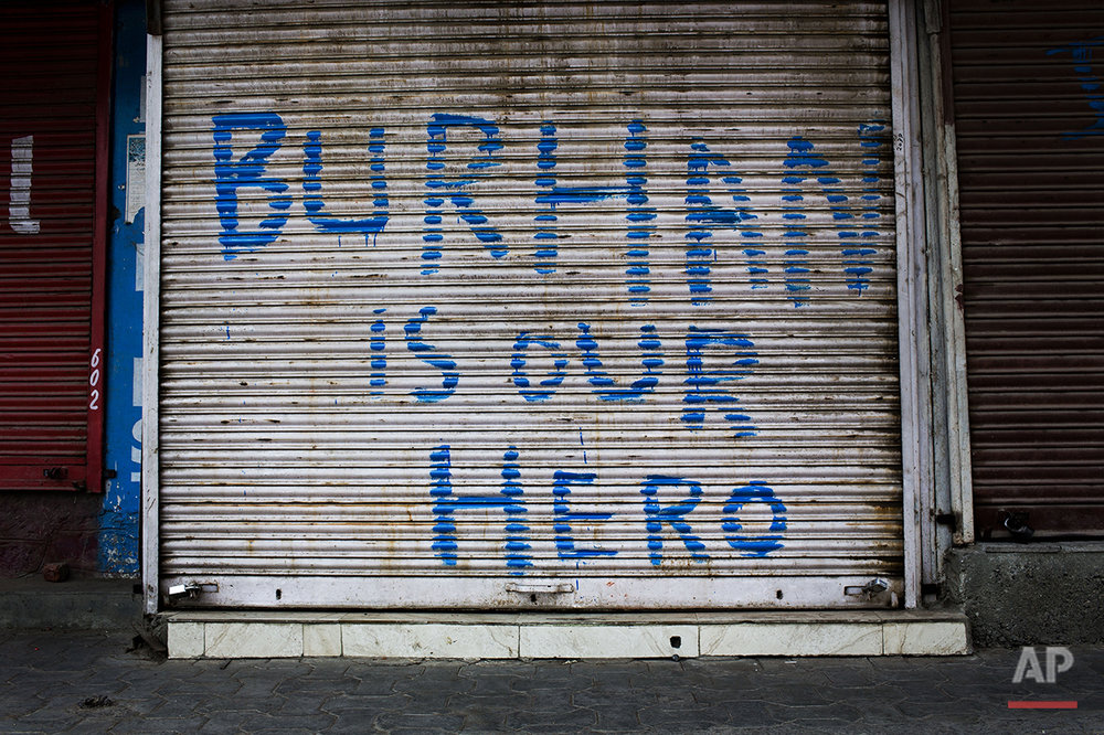 In this July 25, 2016 photo, graffiti is painted on a security shutter of a shop in downtown Srinagar, India-controlled Kashmir. The most recent spate of violence has been the worst in years. It started on July 8, 2016, after Indian soldiers killed Burhan Wani, a charismatic 22-year-old rebel who attracted a following in large part by using the tools of his age, social media. (AP Photo/Bernat Armangue)