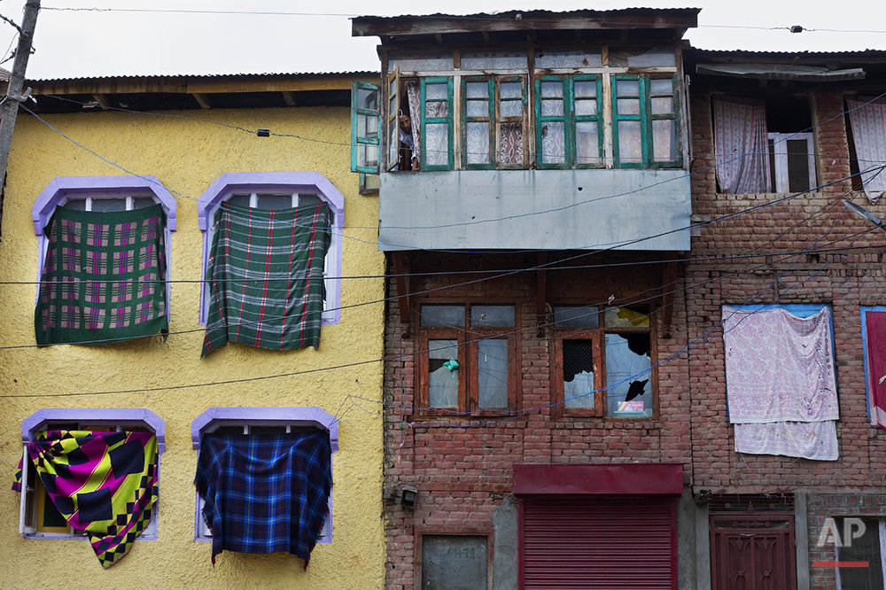 In this July 25, 2016, photo, a Kashmiri man looks from a window in Srinagar, India-controlled Kashmir. Those who live near the most violent areas use blankets to cover their windows to protect the few unbroken panes and prevent projectiles from flying inside. (AP Photo/Bernat Armangue)