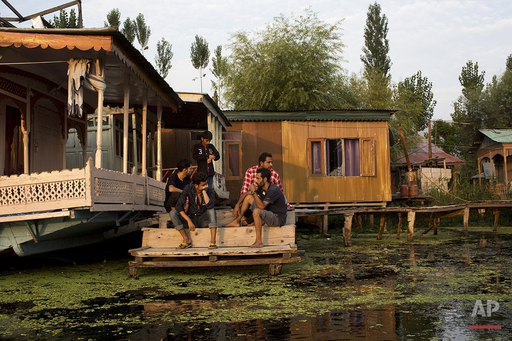 In this July 25, 2016 photo, Kashmiris gather at the docks of the Dal lake in Srinagar, India-controlled Kashmir. In many ways, the lake offers a barometer for the political situation in Kashmir. If the wooden boats, known as Shikharas, are not out on the water and if music isn't floating from the houseboats, then it probably means yet another cycle of violence has come to Kashmir. (AP Photo/Bernat Armangue)