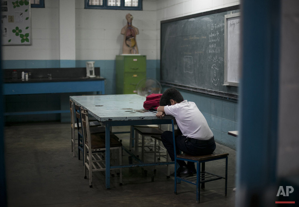 In this June 1, 2016 photo, a student lays his head down during class at a public high school in Caracas, Venezuela. The annual high school dropout rate has doubled to 11 percent since 2011, and schools are understaffed as professionals flee the country. (AP Photo/Ariana Cubillos)