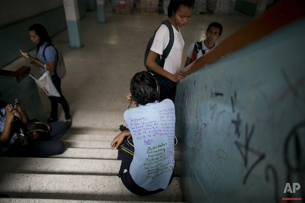 In this May 31, 2016 photo, a student's uniform shirt is covered with messages that were hand written by classmates, an end-of-the-year school ritual, at a public high school in Caracas, Venezuela. A quarter of Venezuelan children missed some school this year because of hunger, according to the local nonprofit Foundation Bengoa. (AP Photo/Ariana Cubillos)