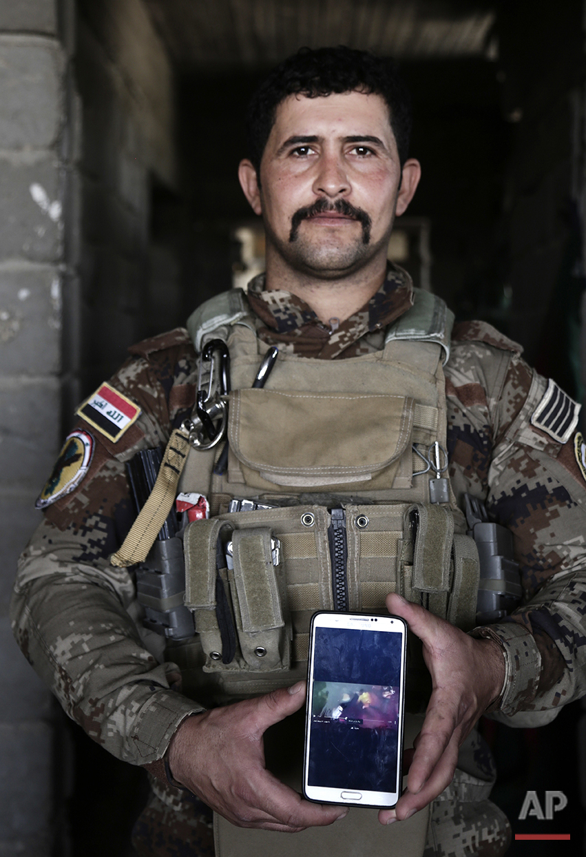 "In this Wednesday, June 8, 2016 photo, Sgt. Ahmed Abdelaziz, 29 of Iraq's elite counterterrorism forces shows an Islamic State video of his brother's death, at a battle position on the southern edge of Fallujah, Iraq. Abdelaziz, has been almost continually deployed fighting the Islamic State group ever since the militants overran nearly a third of Iraq in the summer of 2014. Now he's on the front lines of Fallujah, a city declared ""fully liberated"" on Sunday, June 26, 2016 by the commander leading the fight against IS. Abdelaziz has with him what he always brings into battle: a photo of his brother. (AP Photo/Maya Alleruzzo)"