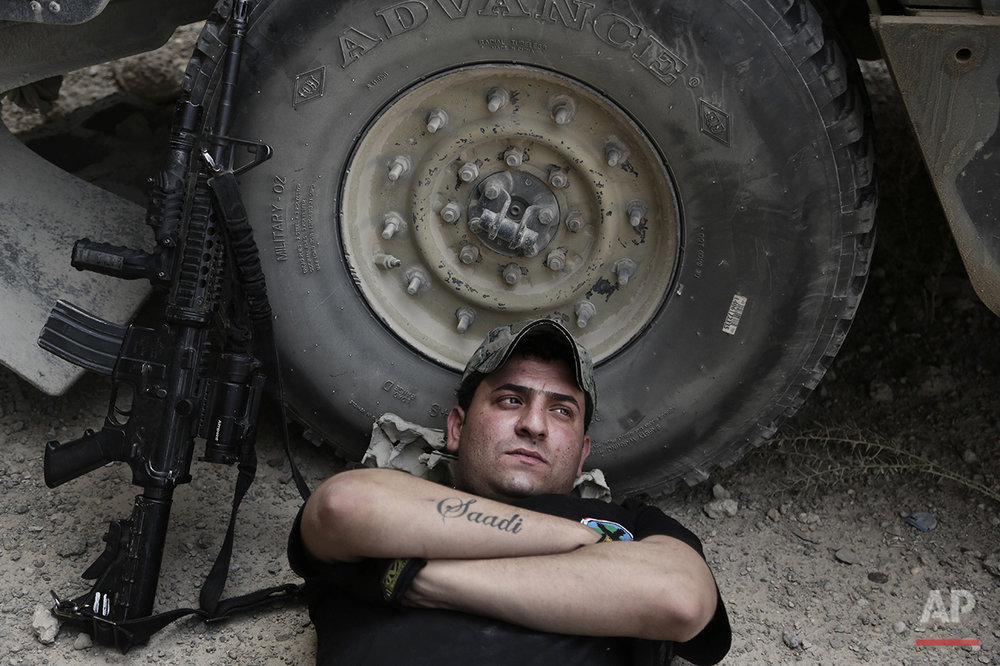 "In this Wednesday, June 8, 2016 photo, Sgt. Ahmed Kamel, 26, of Iraq's elite counterterrorism forces, rests during the midday heat at a battle position on the southern edge of Fallujah, Iraq. He has three tattoos: the name of his brother, Saadi, who was killed by the Mahdi Army in 2008, the name of a comrade, Namar, who was killed fighting the Islamic State group; and the Iraqi flag. A senior Iraqi commander declared that the city of Fallujah was ""fully liberated"" from Islamic State group militants on Sunday, June 26, 2016 after a more than monthlong military operation. (AP Photo/Maya Alleruzzo)"