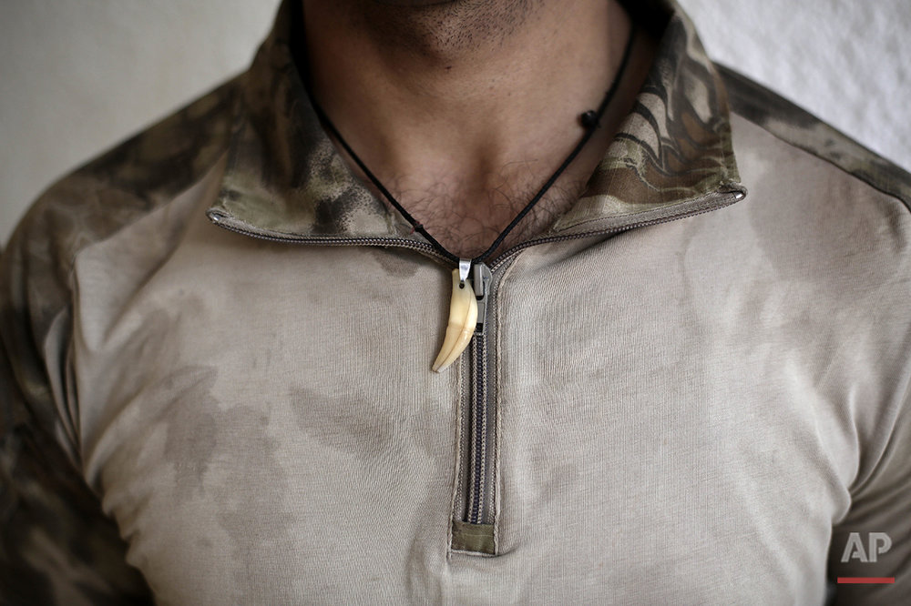"In this Tuesday, June 7, 2016 photo, Pvt. Mustafa Muhammed Saadoun, 21, of Iraq's elite counterterrorism forces shows a wolf's tooth he wears as a good luck charm, after coming back from a mission during the operation to oust the Islamic State group from Fallujah, Iraq. He says the necklace makes him stronger and makes him less fearful. A senior Iraqi commander declared that the city of Fallujah was ""fully liberated"" from Islamic State group militants on Sunday, June 26, 2016 after a more than monthlong military operation. (AP Photo/Maya Alleruzzo)"