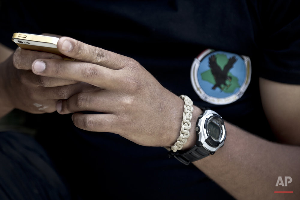 "In this Wednesday, June 8, 2016 photo, 1st Sgt. Muayd Saad wears a watch given to him by his wife as he checks his phone on the southern edge of Fallujah, Iraq during an operation to oust Islamic State militants from the city. ""Most people in Iraq, they just have faith in God and they don't feel like they need things like this,"" he said, explaining why some of his friends who aren't in the military don't understand why he considers the watch his wife gave him on their anniversary to be good luck. ""In the whole fight against IS, I have never taken it off, not even to sleep,"" he said. A senior Iraqi commander declared that the city of Fallujah was ""fully liberated"" from Islamic State group militants on Sunday, June 26, 2016 after a more than monthlong military operation. (AP Photo/Maya Alleruzzo)"