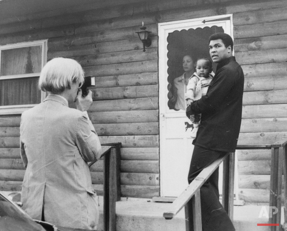 Pop artist Andy Warhol, left, is shown photographing Muhammad Ali, his infant daughter, Hanna, and wife, Veronica, Thursday, August 18, 1977, at Ali's training camp in Deer Lake, Pa. (AP Photo)