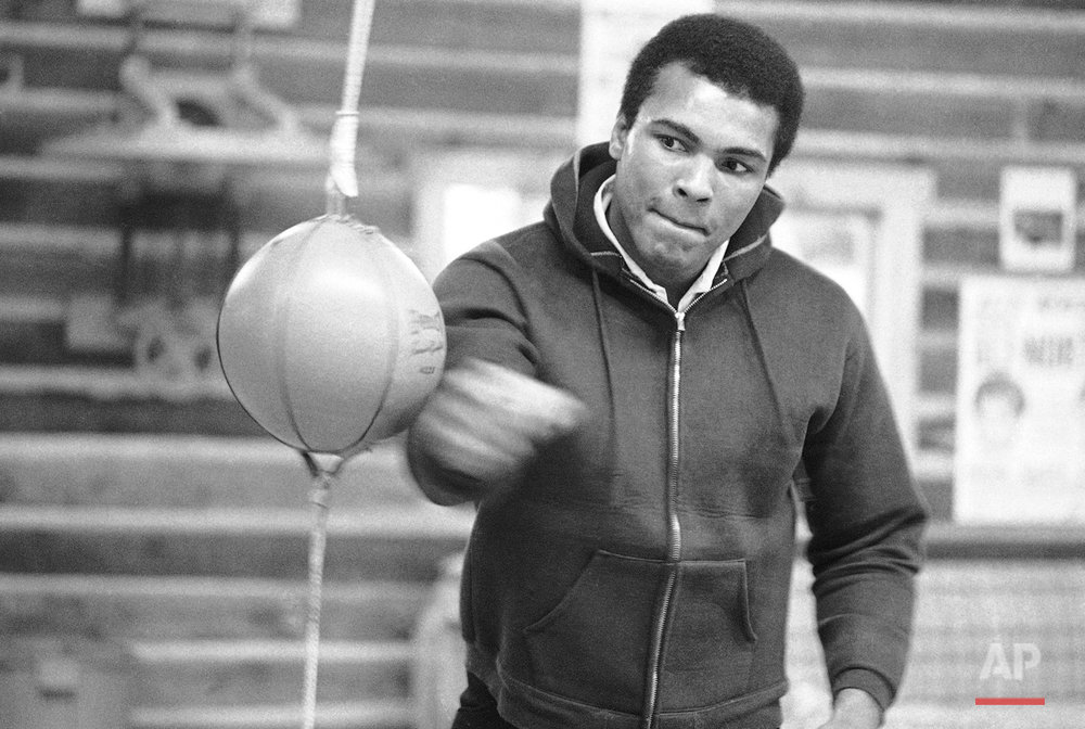 With compressed lips, Muhammad Ali punches bag on Jan. 10, 1974 in his Deer Lake, Pa., training camp where he is preparing for his January 28 rematch with Joe Frazier. Ali still broods about his defeat by Frazier back in March 1971 but says he is going to win this time. (AP Photo/ Rusty Kennedy)