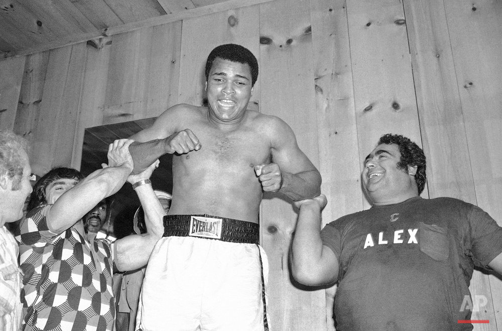 Muhammad Ali gets a lift from Russian Olympic weightlifting champion Vasily Alexeev, right, and Vartan Militosian, left, also of the USSR, at Deer Lake, Pa., Aug. 7, 1978. Both men were part of a group of ten weightlifting champions from the USSR, Hungary and West Germany who are passing through to Las Vegas for their on August 11th international weightlifting tournament. Ali will fight Leon Spinks in New Orleans on September 15th. (AP Photo/Marty Lederhandler)