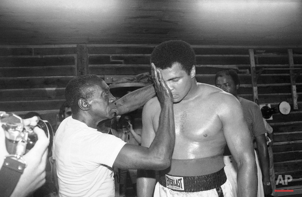 "Unidentified handler brushes sweat from Muhammad Ali's face, Aug. 16, 1978, as he trains at his Deer Lake, Pa. camp for comeback bout with Leon Spinks in New Orleans on September 15. Ali, who claims he was out of shape for the last heavyweight title match with Spinks, says he will be in top form for the next one and plans to make ""real history"" by regaining the title for an unprecedented third time. (AP Photo/Dave Pickoff)"
