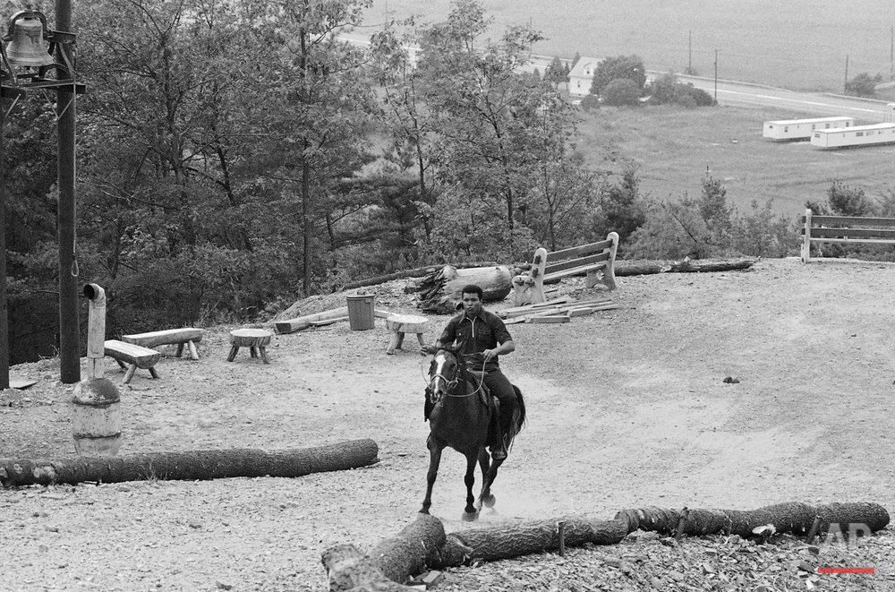 In this Aug. 21, 1973 photo, boxer Muhammad Ali takes a ride on a horse at his training camp at Deer Lake, Pa. Since Ali's death last week at 74, residents have been coming to the rustic hilltop camp in Deer Lake to pay their respects. (AP Photo/John Rous)