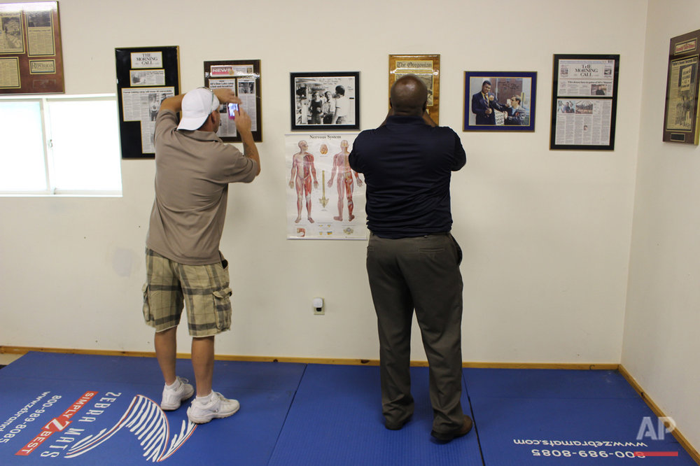 In this photo taken Monday, June 6, 2016, visitors take photos inside the gym at Muhammad Aliís training camp in Deer Lake, Pa. Since Aliís death at 74, residents have been coming to the rustic hilltop camp to pay their respects. (AP Photo/Michael Rubinkam)  (AP Photo/Michael Rubinkam)