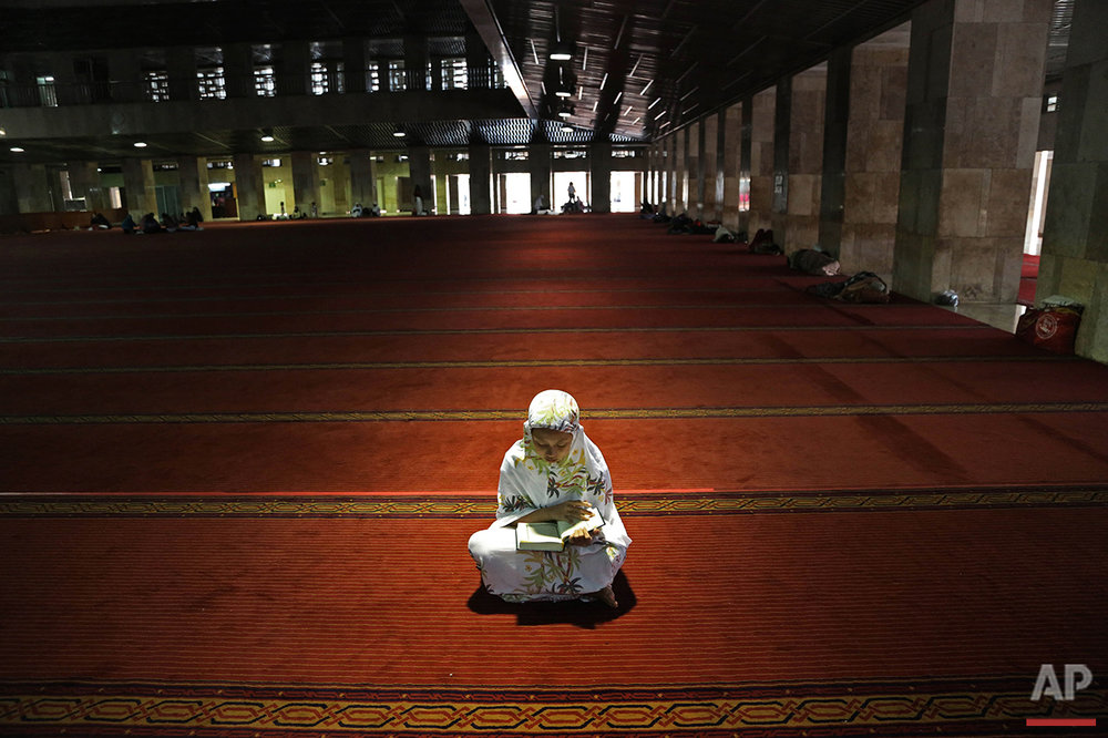 A Muslim woman reads the Quran following noon prayers on the first day of the holy fasting month of Ramadan at Istiqlal Mosque in Jakarta, Indonesia, Monday, June 6, 2016. During Ramadan, the holiest month on Islamic calendar, Muslims refrain from eating, drinking, smoking and sex from dawn to dusk. (AP Photo/Tatan Syuflana)