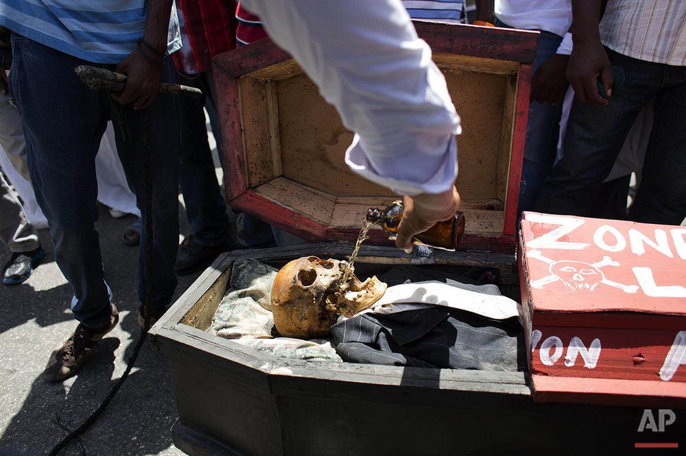 A supporter of PHTK presidential candidate Jovenel Moise pours beer into a skeleton representing interim President Jocelerme Privert in a mock coffin, during a voodoo ceremony before the start of a protest march demanding his resignation in Port-au-Prince, Haiti, Tuesday, June 7, 2016. The electoral council of Haiti has decided to re-do a presidential election that a special commission determined was marred by fraud. (AP Photo/Dieu Nalio Chery)