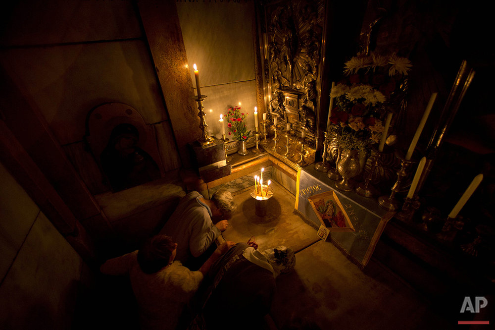 Christians pray at Jesus' tomb as a team of experts begins renovation of the structure in the Church of the Holy Sepulchre in Jerusalem's old city, Monday, June 6, 2016. The renovation required longstanding religious rivalries to be put aside to carry out the first repairs at the site in over 200 years. (AP Photo/Ariel Schalit)