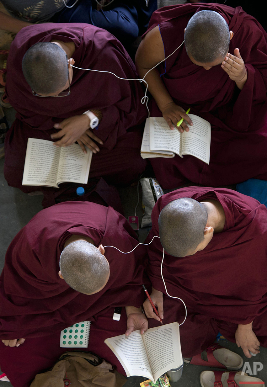 Exiled Tibetan Buddhist nuns read a religious text as they use headphones to listen to their spiritual leader, the Dalai Lama, during a religious talk at the Tsuglakhang temple in Dharmsala, India, Thursday, June 9, 2016. (AP Photo /Ashwini Bhatia)