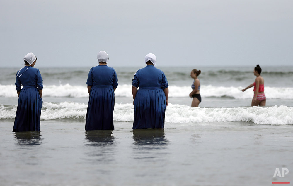 From left, Joanne Steury, Margerie Steury and Rosa Graber stand in Pacific Ocean waters for the first time during a family trip from their Amish community in Michigan, to Coronado, Calif., on Thursday, June 9, 2016. (AP Photo/Gregory Bull)