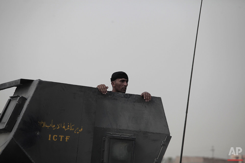 A soldier with Iraq's elite counterterrorism forces peers from the gun turret of a Humvee on the front line in Fallujah, Iraq, Sunday, June 5, 2016. Iraqi forces are pushing their way into the city to retake it from Islamic State militants. (AP Photo/Maya Alleruzzo)