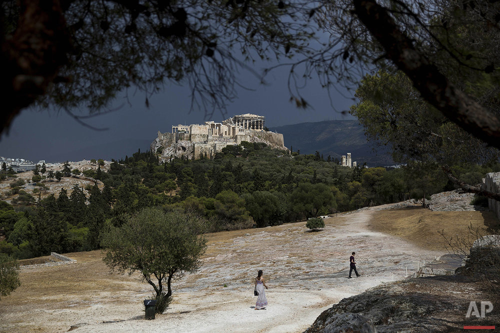 People walk on Pnyx hill in front of the ancient Acropolis hill and the ruins of the fifth century B.C. Parthenon temple in Athens on Tuesday, June 7, 2016. Beginning as early as 507 BC, the Athenians gathered on the Pnyx to host their popular assemblies, thus making the hill one of the earliest and most important sites in the creation of democracy. (AP Photo/Petros Giannakouris)