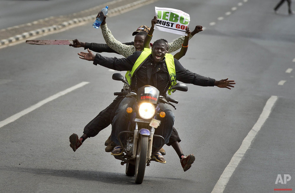 Protesters on a motorcycle hold a placard using the acronym of the national electoral commission as they drive ahead of others on foot calling for the disbandment of the commission over allegations of bias and corruption, in downtown Nairobi, Kenya on Monday, June 6, 2016. (AP Photo/Ben Curtis)