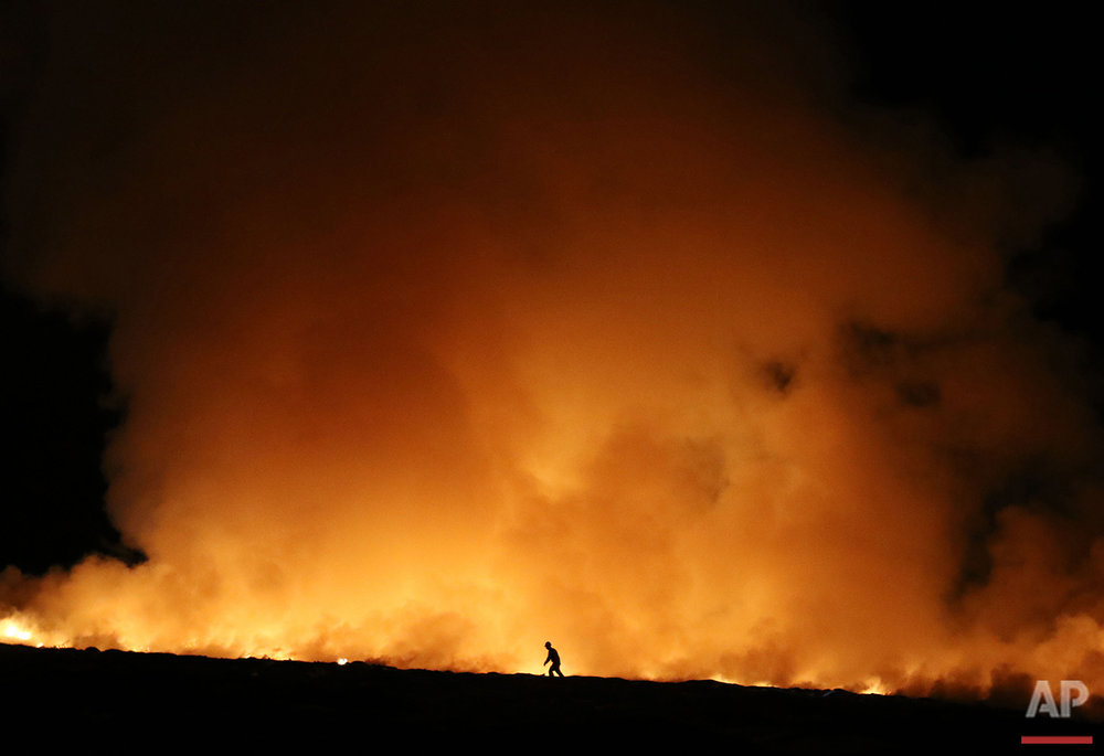 A firefighter walks past flames at the Douglas County landfill in Roseburg, Ore. on Saturday, June 4, 2016. (Michael Sullivan/The News-Review via AP)