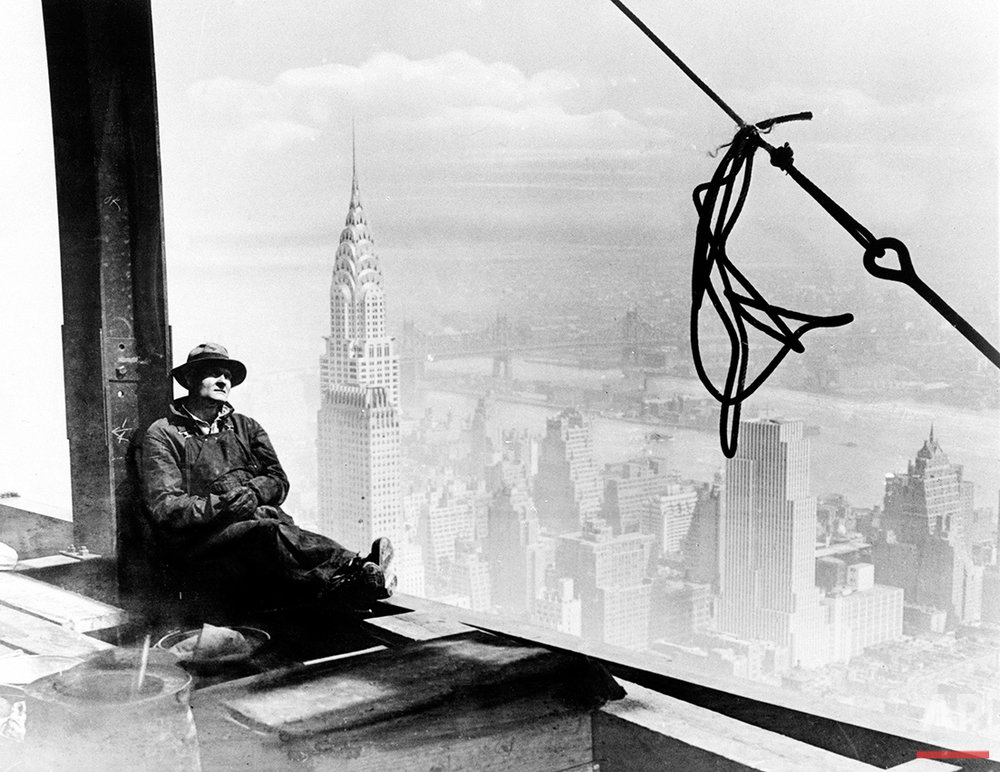 A steel worker rests on a girder at the 86th floor of the new Empire State Building during construction in New York City, Sept. 24, 1930. The tower of the Chrysler Building can be seen in the background on left.  (AP Photo)