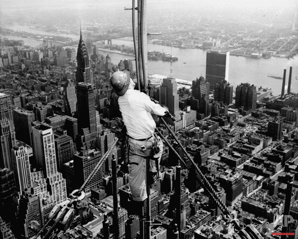 High over Manhattan, a workman is busy on construction for the Empire State Building's new 217 foot multiple television tower, September 28, 1950. The tower, to be ready in December, will increase the building's height to 1,467 feet. (AP Photo)
