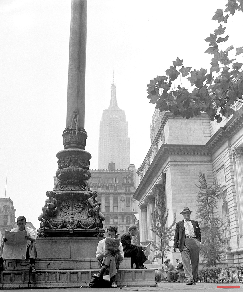 New York City, known the world over for its hustle-and-bustle, has its peaceful side also. Here a group of men take time out from their daily work to relax and read as they sit on the base of the flagpole on the New York Public Library grounds, Sept. 19, 1951. In the background is the towering structure of the Empire State building. (AP Photo/Robert Kradin)