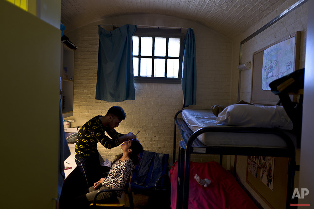 In this Sunday, May 1, 2016 photo, Yazidi refugee Yassir Hajji, 24, from Sinjar, Iraq, adjusts the eyebrow of his wife Gerbia,18, in their room in the former prison of De Koepel in Haarlem, Netherlands. (AP Photo/Muhammed Muheisen)