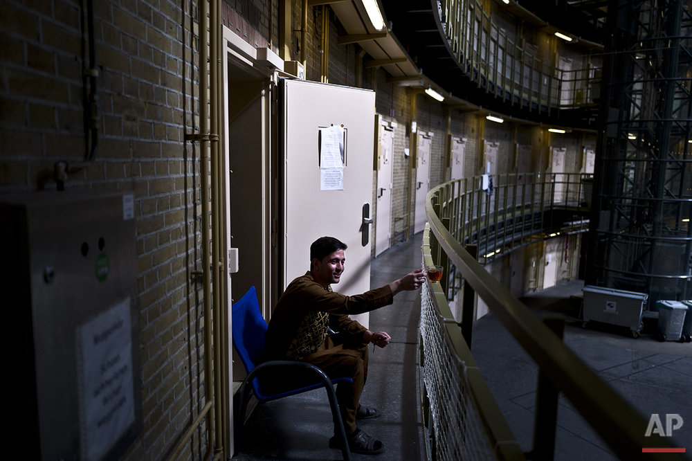 In this Sunday, May 1, 2016 photo, Afghan refugee Siratullah Hayatullah, 23, drinks tea by the doorway of his room at the former prison of De Koepel in Haarlem, Netherlands. (AP Photo/Muhammed Muheisen)