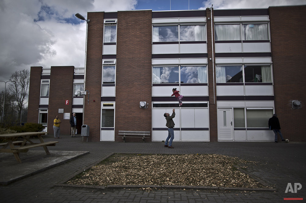 In this Friday, April 8, 2016 photo, a migrant plays with a girl at the former prison of Westlingen in Heerhugowaard northwestern Netherlands. (AP Photo/Muhammed Muheisen)