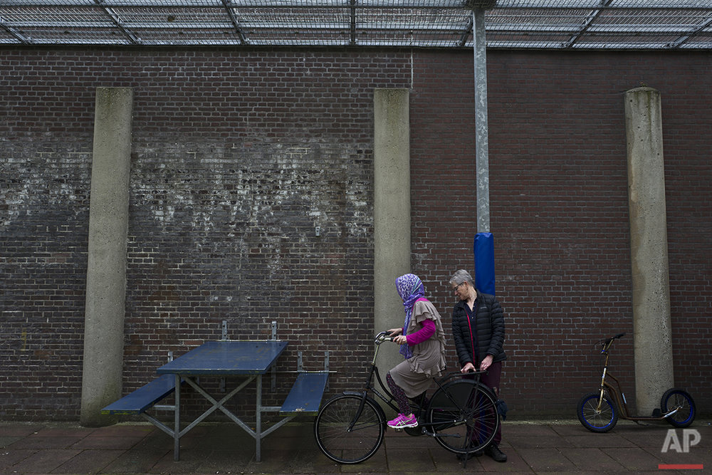 In this Monday, May 2, 2016 photo, a Dutch volunteer teaches an Afghan refugee woman how to ride a bicycle at a yard in the former prison of De Koepel in Haarlem, Netherlands. (AP Photo/Muhammed Muheisen)