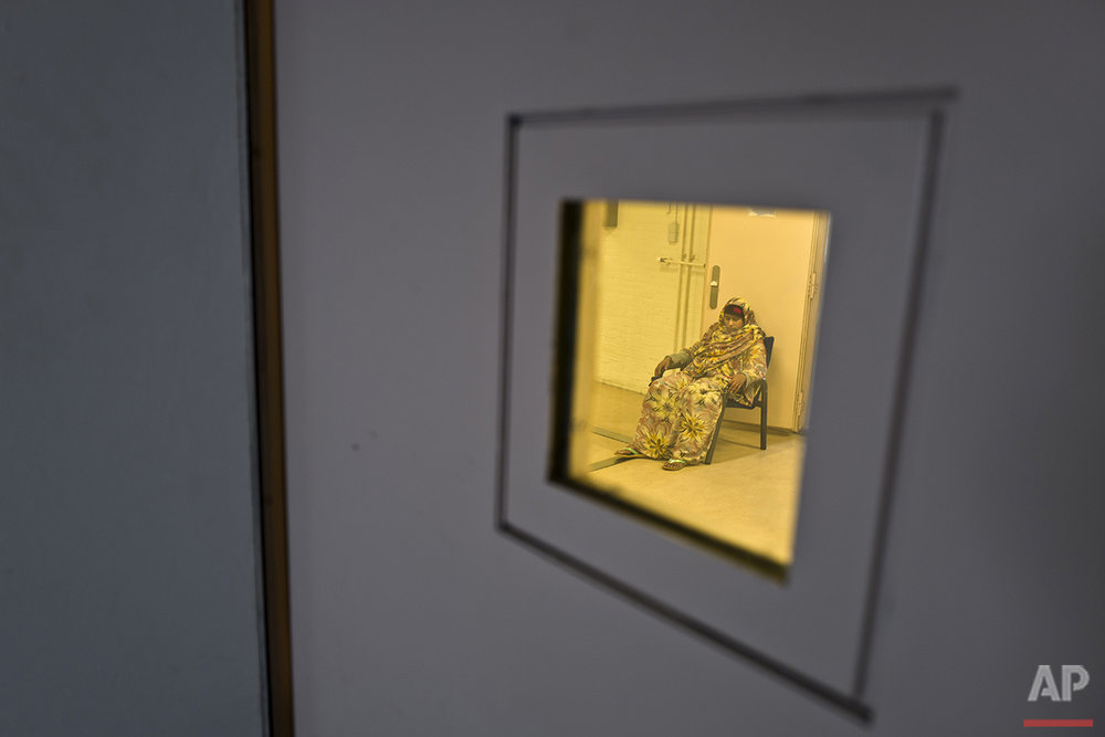 In this Tuesday, April 26, 2016 photo, Somali migrant Ijaawa Mohamed, 41, sits on a chair outside a room at the women section of the former prison of De Koepel in Haarlem, Netherlands. (AP Photo/Muhammed Muheisen)