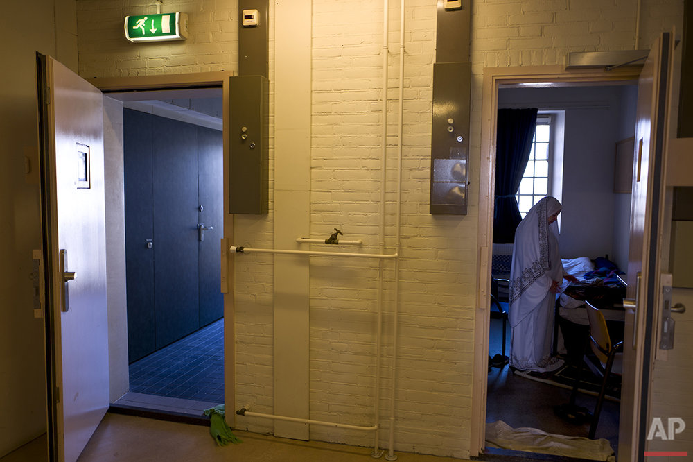 In this Wednesday, April 20, 2016 photo, Iraqi refugee Fatima Hussein, 65, prays inside her room at the former prison of De Koepel in Haarlem, Netherlands. (AP Photo/Muhammed Muheisen)