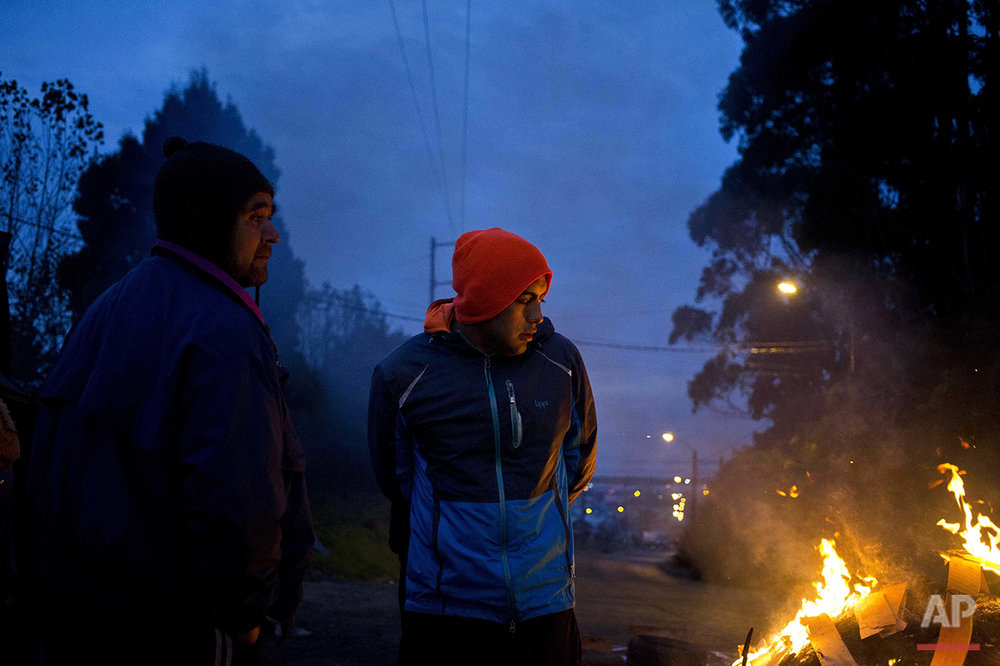 "In this May 10, 2016 photo, diver Jose Luis Cifuentes, takes part in a protest in Ancud, on Chile's Chiloe Island, during the country's worst ever ""red tide"" environmental disaster. Food and gasoline have been scarce after small-scale fishermen blocked the island from the mainland, lighting flaming barricades for days to demand more compensation from the government. (AP Photo/Esteban Felix)"