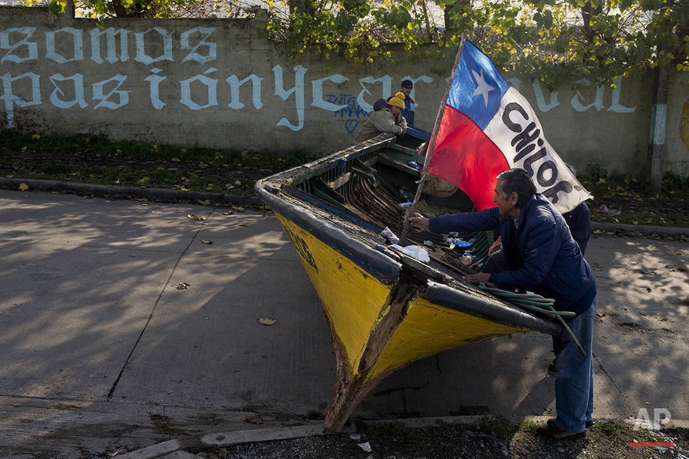 "In this May 6, 2016 photo, a fisherman places a Chilean national flag in his boat that is serving as a barricade, blocking a road in Ancud in Chile's Chiloe Island, during the country's worst ever ""red tide"" environmental disaster. (AP Photo/Esteban Felix)"