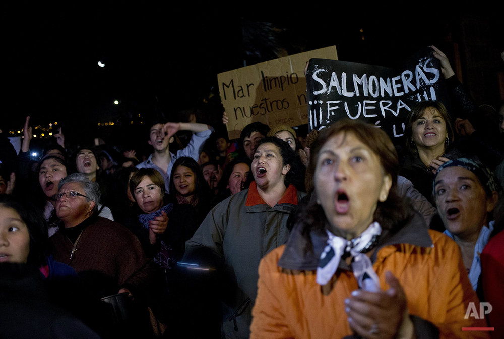 "In this May 9, 2016 photo, residents shout anti-government slogans as they protest in Ancud, Chile's Chiloe Island, during the country's worst ever ""red tide"" environmental disaster. The government has offered about $220 a month to some 5,000 local fishermen as compensation, but they're demanding twice that, saying the offer isn't enough to cover basic needs. (AP Photo/Esteban Felix)"