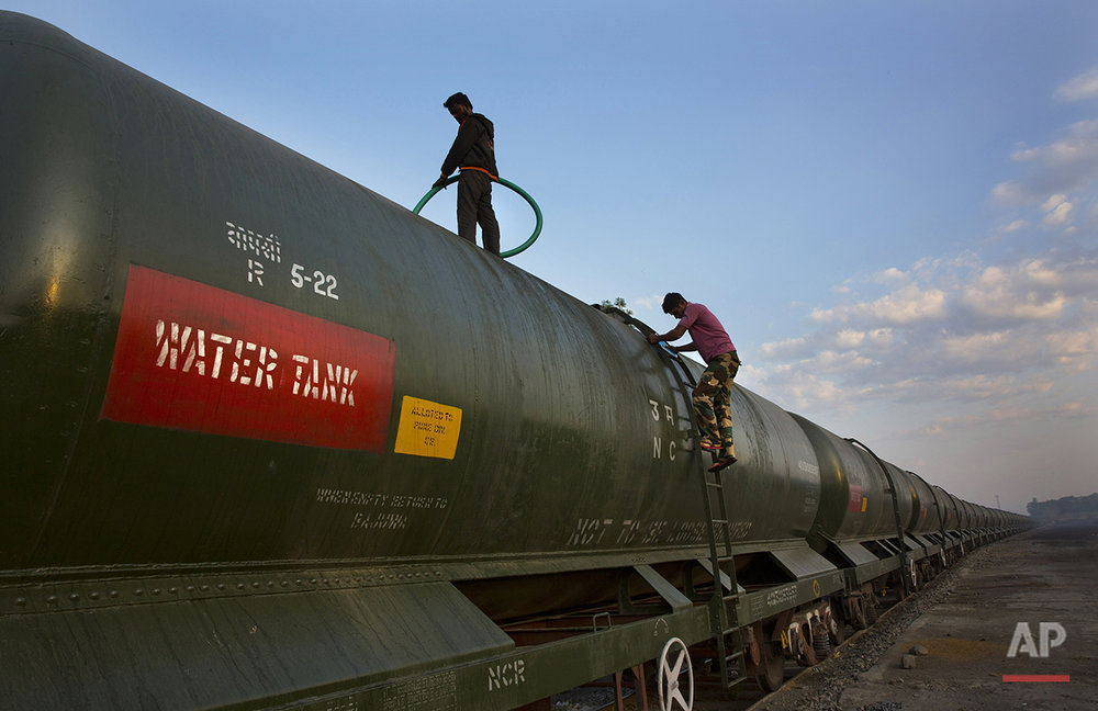 "In this May 9, 2016, photo, workers fill a water tank on the Jaldoot water train at the Miraj railway station, Miraj, 340 kilometers (211 miles) from Latur, in the Indian state of Maharashtra. Many trains pull into Latur's railroad station but none is as eagerly awaited as this train that pulls into the parched town in the dead of the night. That train called ""Jaldoot"" or the Messenger of Water brings millions of liters of the precious liquid that the drought-plagued central Indian district so desperately needs. (AP Photo/Manish Swarup)"