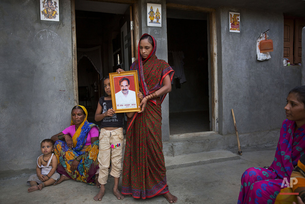 "In this May 10, 2016, photo, Rajana Umesh Jadav, 30, center, with her daughter Shruti, 10, and son Shitij, 4, left, shows the portrait of her husband Umesh Navnath Jadav, who fell into a well while fetching water at a village on the outskirts of Latur, in the Indian state of Maharashtra. Many trains pull into Latur's railroad station but none is as eagerly awaited as this train that pulls into the parched town in the dead of the night. That train called ""Jaldoot"" or the Messenger of Water brings millions of liters of the precious liquid that the drought-plagued central Indian district so desperately needs. (AP Photo/Manish Swarup)"