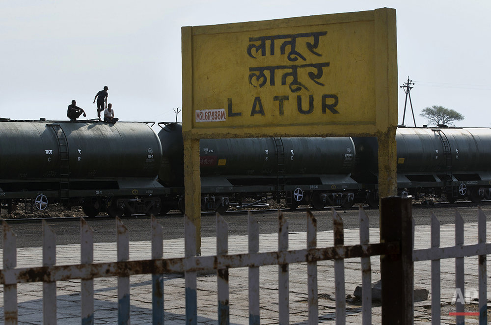 "In this May 10, 2016, photo, workers sit on the top of a tanker carriage after unloading the water from the Jaldoot water train at the Latur railway station, in the Indian state of Maharashtra. Many trains pull into Latur's railroad station but none is as eagerly awaited as this train that pulls into the parched town in the dead of the night. That train called ""Jaldoot"" or the Messenger of Water brings millions of liters of the precious liquid that the drought-plagued central Indian district so desperately needs. (AP Photo/Manish Swarup)"