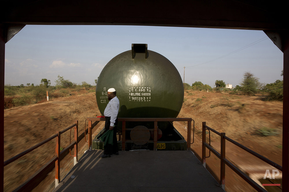 "In this May 9, 2016, photo, Sikandar Nabi Sahab, guard of the Jaldoot water train, looks out at the parched lands from a platform as the train rolls out of Miraj railway station, Miraj,  340 kilometers (211 miles) from Latur, in the Indian state of Maharashtra. Many trains pull into Latur's railroad station but none is as eagerly awaited as this train that pulls into the parched town in the dead of the night. That train called ""Jaldoot"" or the Messenger of Water brings millions of liters of the precious liquid that the drought-plagued central Indian district so desperately needs. (AP Photo/Manish Swarup)"