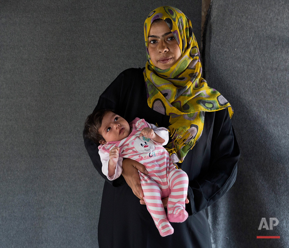 In this picture made on Sunday, May 15, 2016, 24-year-old Asmaa, a Syrian mother from Damascus, poses with her baby girl Jana in a tent made of blankets given by the UNCHR at the refugee camp of the northern Greek border point of Idomeni. Asmaa is one of the dozens of refugee women that gave birth while stranded in Idomeni after the Greek- Macedonian border was closed in early March 2016. Jana, the family's third child, was born on Thursday, March 24, 2016 in the hospital of the nearby town of Kilkis. The five member family wants to go to Germany. (AP Photo/Petros Giannakouris)