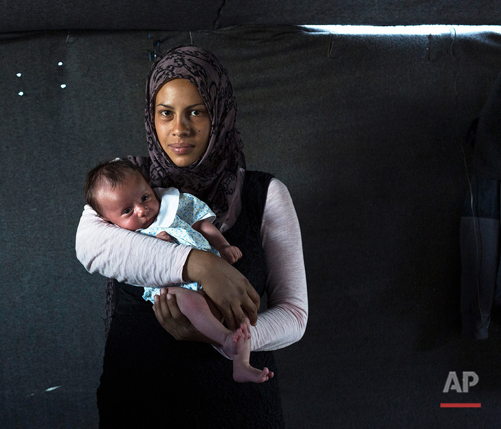 In this picture made on Thursday, May 12, 2016, 19-year-old Rajad Alhelo, a Syrian mother from the city of Deir ez-Zor poses with her baby girl Yasmin in a tent made of blankets given by the UNCHR at the refugee camp of the northern Greek border point of Idomeni. Rajad Alhelo is one of the dozens of refugee women that gave birth while stranded in Idomeni after the Greek- Macedonian border was closed in early March 2016. Yasmin, the family's first child, was born on Friday, April 1, 2016 in the hospital of the nearby town of Kilkis. The three member family wants  to go to Germany or any other safe place in central Europe.(AP Photo/Petros Giannakouris)
