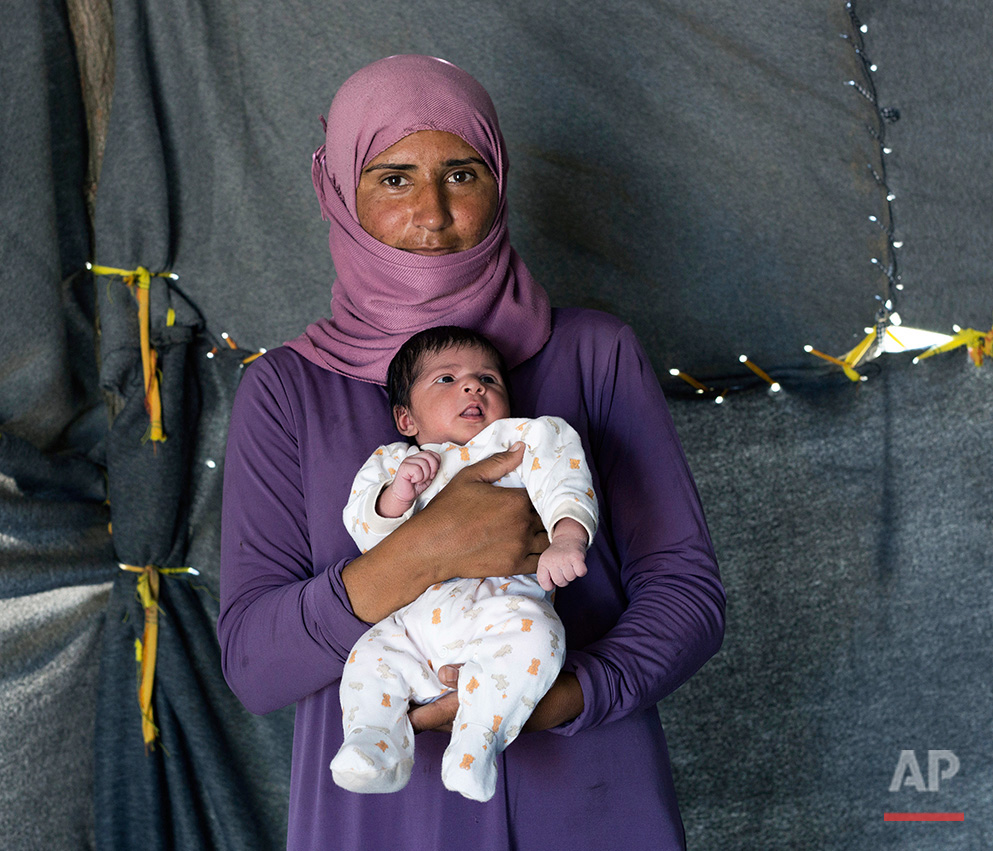In this picture made on Sunday, May 15, 2016, 28-year-old Samar, a Syrian mother from the city of Deir ez-Zor , poses with her baby girl Sedan, in a tent made of blankets given by the UNCHR at the refugee camp of the northern Greek border point of Idomeni. Samar  is one of the dozens of refugee women that gave birth while stranded in Idomeni after the Greek- Macedonian border was closed in early March 2016.  Sedan the Family's forth child  was born on Tuesday, May 3, 2016  in the hospital of the nearby town of Kilkis. Samar's husband has been in Germany the last seven months but she has not heard from him since she arrived in Greece. (AP Photo/Petros Giannakouris)
