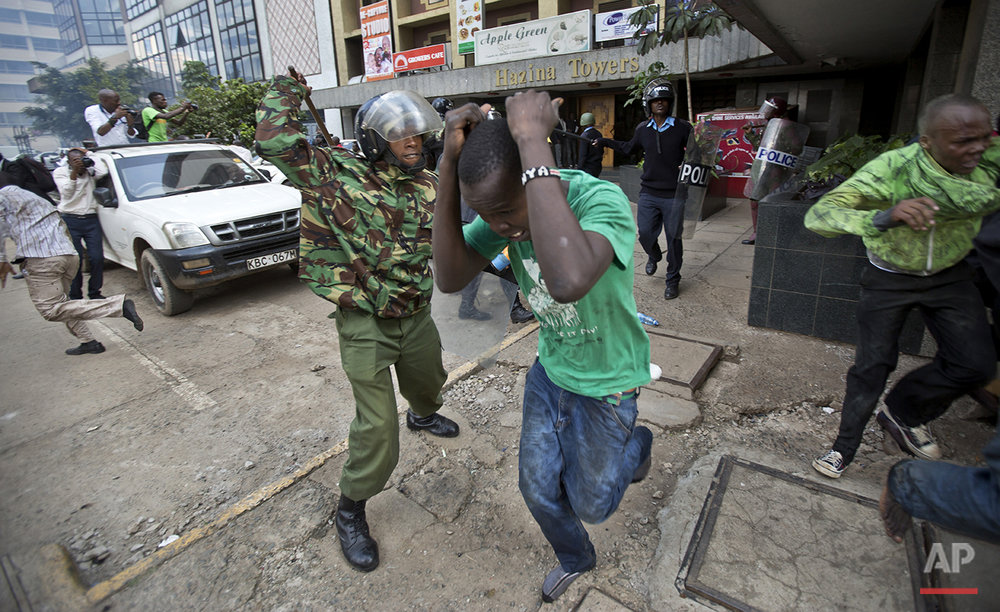 Opposition supporters are beaten with wooden clubs by riot police as they try to flee, during a protest in downtown Nairobi, Kenya Monday, May 16, 2016. Kenyan police have tear-gassed and beaten opposition supporters during a protest demanding the disbandment of the electoral authority over alleged bias and corruption. (AP Photo/Ben Curtis)