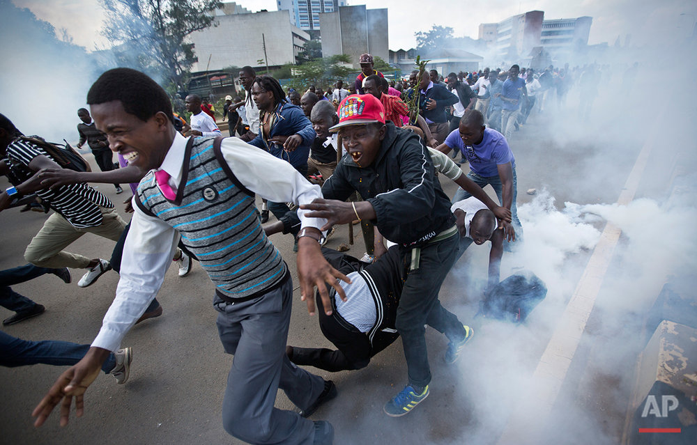 Opposition supporters flee from tear gas grenades fired by riot police, during a protest in downtown Nairobi, Kenya Monday, May 16, 2016. Kenyan police have tear-gassed and beaten opposition supporters during a protest demanding the disbandment of the electoral authority over alleged bias and corruption. (AP Photo/Ben Curtis)