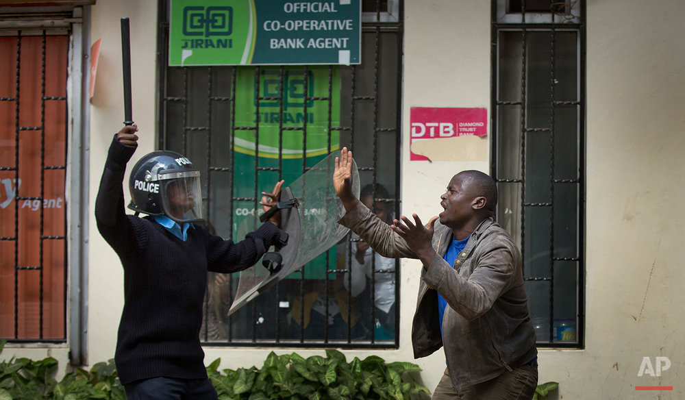 An opposition supporter pleads with a riot policeman, after being beaten with a wooden club by one then managing to escape but then being cornered by another, during a protest in downtown Nairobi, Kenya Monday, May 16, 2016. Kenyan police have tear-gassed and beaten opposition supporters during a protest demanding the disbandment of the electoral authority over alleged bias and corruption. (AP Photo/Ben Curtis)