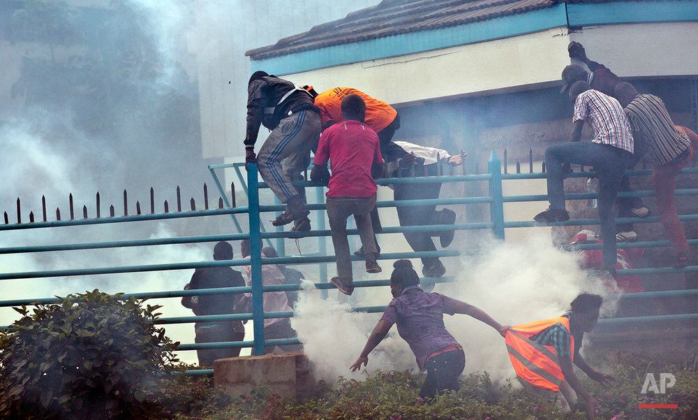 Opposition supporters climb over a fence into the University of Nairobi campus, as they flee from clouds of tear gas fired by riot police, during a protest in downtown Nairobi, Kenya Monday, May 16, 2016. Kenyan police have tear-gassed and beaten opposition supporters during a protest demanding the disbandment of the electoral authority over alleged bias and corruption. (AP Photo/Ben Curtis)