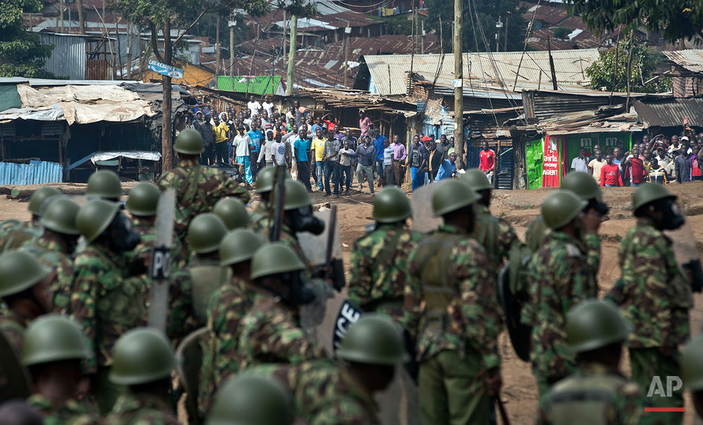 Kenyan police prepare to charge as they engage in running battles between police firing tear gas and protesters throwing rocks, in the Kibera slum of Nairobi, Kenya Monday, May 23, 2016. Kenya's police shot, beat and tear gassed opposition demonstrators across the country who tried to gather to call for the electoral commission to be dissolved due to allegations of bias and corruption. (AP Photo/Ben Curtis)