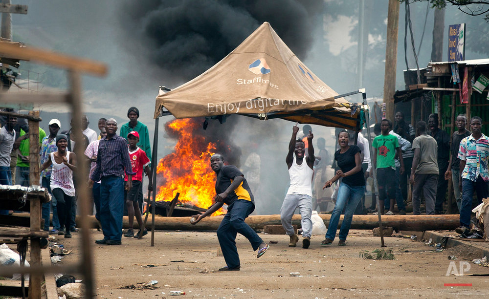 Opposition protesters throw rocks in front of barricades of burning tires, as they engage in running battles with police firing tear gas, in the Kibera slum of Nairobi, Kenya Monday, May 23, 2016. Kenya's police shot, beat and tear gassed opposition demonstrators across the country who tried to gather to call for the electoral commission to be dissolved due to allegations of bias and corruption. (AP Photo/Ben Curtis)